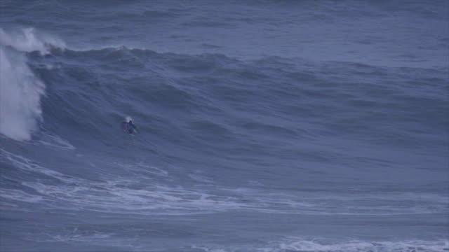 a surfer gets wiped out while paddling surfing waves on his surfboard. - falla av bildbanksvideor och videomaterial från bakom kulisserna
