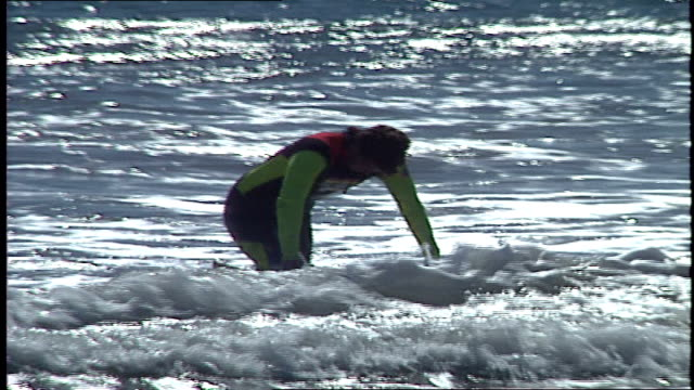 surfer getting out of water with board malibu california - water sports equipment stock videos and b-roll footage