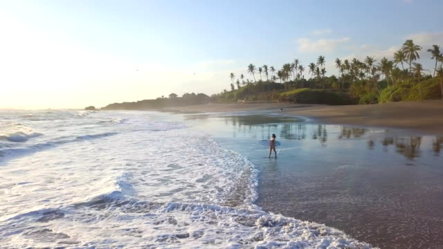 surfer girl bali going into the water side view - bali stock videos & royalty-free footage