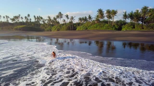 Surfer Mädchen in Bali geht ins Wasser