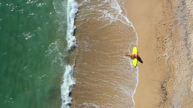 surfer mädchen entspannen nach einem ganzen tag surfen - surfbrett stock-videos und b-roll-filmmaterial