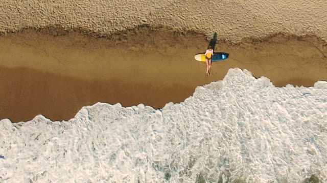 Surfer girl relaxing on the beach 4K