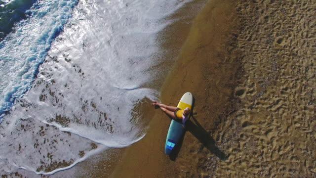 Surfer girl resting on the beach 4K