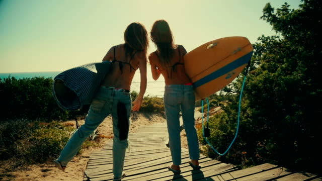 Surfer girls high-five and go to the waves