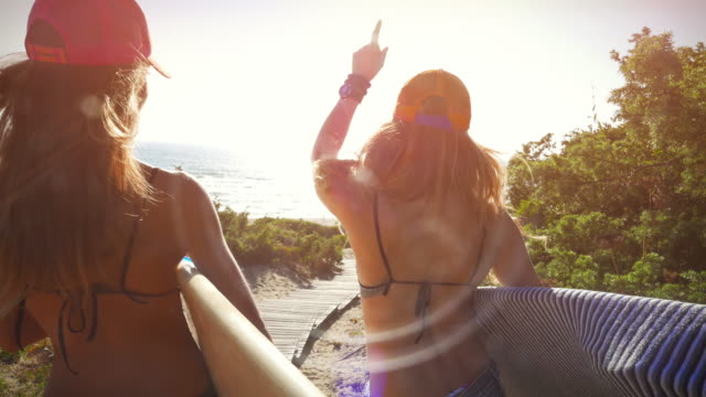 Surfer girls high-five and go