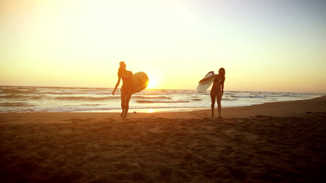 Surfer girls on the beach at sunset