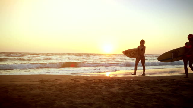 surfer girls on the beach at sunset - surfboard stock videos & royalty-free footage