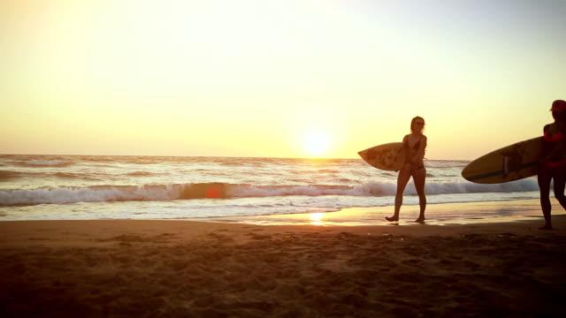 surfer mädchen am strand bei sonnenuntergang - surfbrett stock-videos und b-roll-filmmaterial