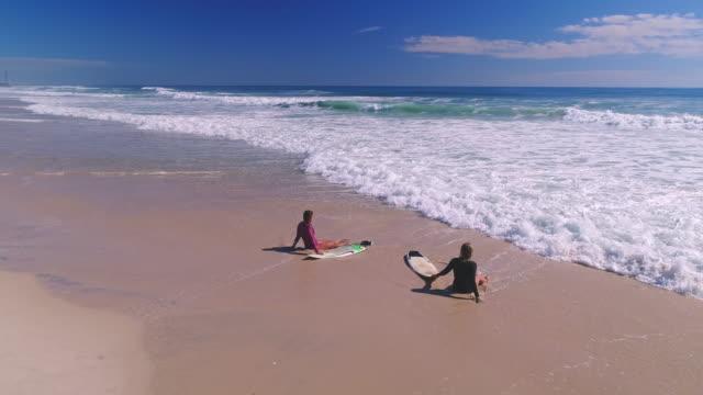 vídeos y material grabado en eventos de stock de chicas surfer relajantes en la playa - gold coast
