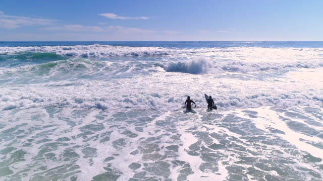 Surfer-Girls laufen ins Meer