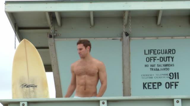 vídeos y material grabado en eventos de stock de ms ts surfer grabbing his board and walking down lifeguard ramp / manhattan beach, california, usa - objeto fabricado