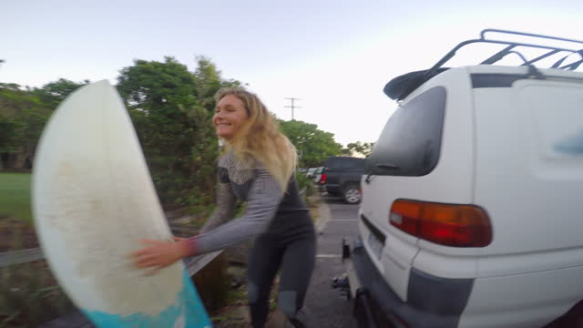 a surfer hiding a car key in a lock box before surfing waves on his surfboard. - 隠れる点の映像素材/bロール