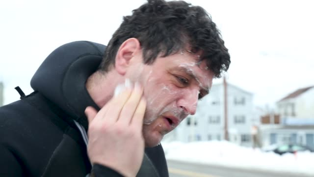 surfer in cold weather putting wax on face - diving suit stock videos and b-roll footage