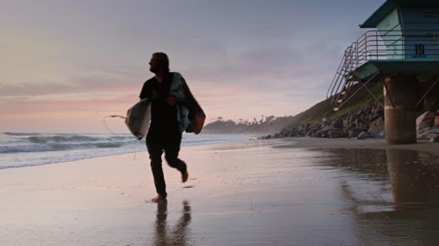 surfer, die joggen durch wasser bei sonnenuntergang - san diego stock-videos und b-roll-filmmaterial