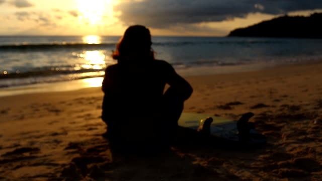 サーファーは、日没時間、ソフト フォーカスで海の波を見てください。 - ソフトフォーカス点の映像素材/bロール