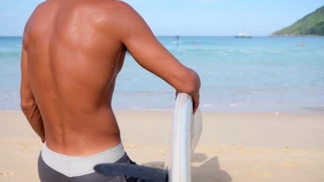 stockvideo's en b-roll-footage met surfer op zoek naar de golf van het strand - big wave surfing