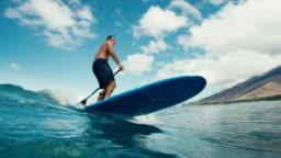 Surfer on blue ocean wave stand up paddleboarding
