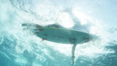 vídeos y material grabado en eventos de stock de surfer paddles on board, shot from underneath - surf