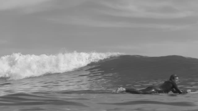 a surfer paddling and surfing waves on his classic longboard surfboard. - slow motion - pagaiare video stock e b–roll