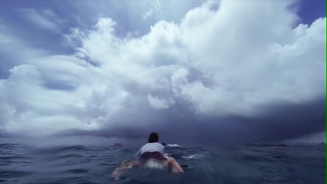 Surfer Paddling Out To Sea - Storm Approaches
