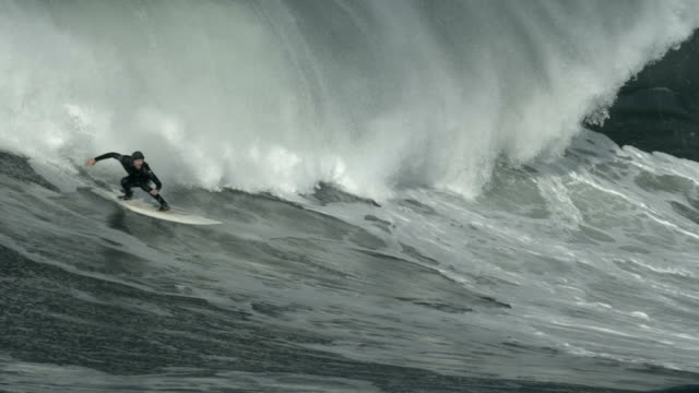 a surfer rides a big wave as it rolls in. - groß stock-videos und b-roll-filmmaterial