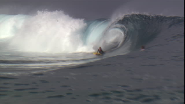 a surfer rides a wave over the south pacific ocean. - south pacific ocean stock videos & royalty-free footage
