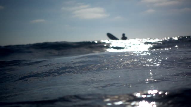 A surfer rides the breaking waves in the surf at the beach. - Slow Motion