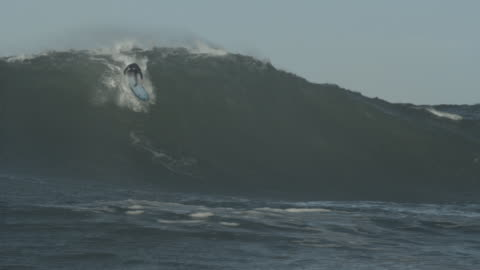 surfer rides the crest of a huge wave as it rolls over. - large stock videos & royalty-free footage