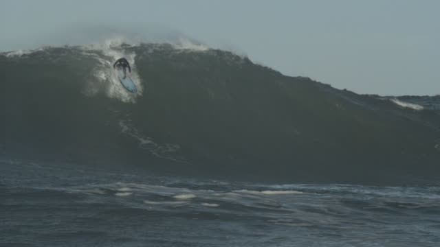 surfer rides the crest of a huge wave as it rolls over. - groß stock-videos und b-roll-filmmaterial