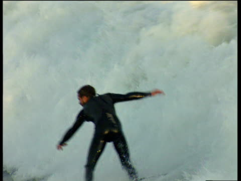 vidéos et rushes de surfer rides wave into white wash water that splashes around him then falls in to sea - lutte concepts