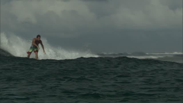 vídeos y material grabado en eventos de stock de surfer rides wave towards shore, pohnpei, fsm - bañador de natación