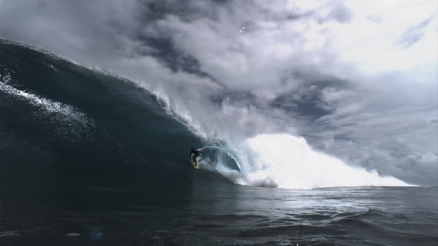 A surfer riding through a wave tube. Available in HD.