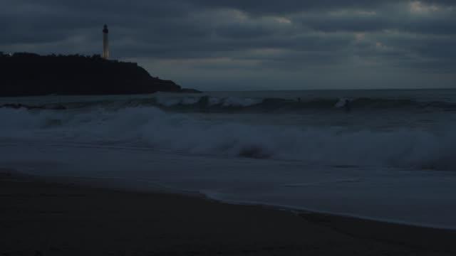 vidéos et rushes de surfer riding wave at night 4k video - lighthouse