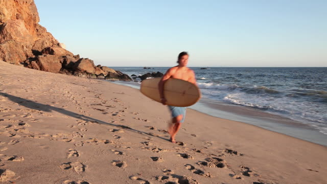 surfer running along a beach - real time stock videos & royalty-free footage
