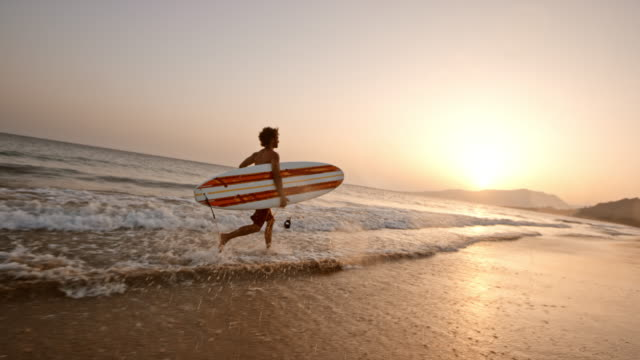 SLO MO Surfer running in shallow water on a beach while holding his surf board at sunset