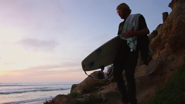 Surfer Scrambling Down to Beach at Sunset
