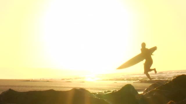 vídeos y material grabado en eventos de stock de surfer silhouetted against sunny backdrop - pipeline wave