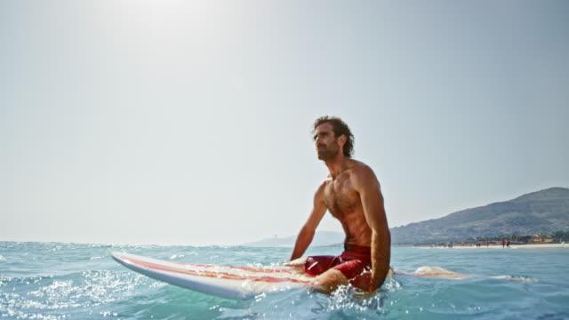 slo-mo-surfer auf seinem brett im meer in der sonne sitzen - surfbrett stock-videos und b-roll-filmmaterial