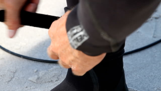cu surfer strapping leash to ankle, cape town, south africa - 鎖点の映像素材/bロール
