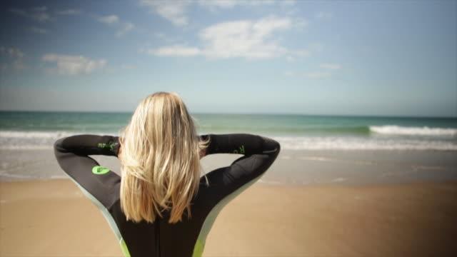 vídeos de stock, filmes e b-roll de surfer stretching before surf - traje de mergulho