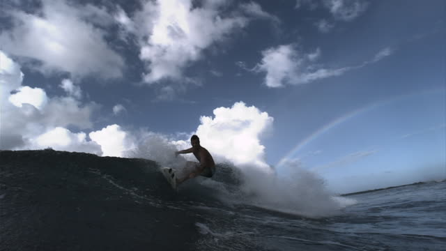 A surfer successfully rides a wave. Available in HD.