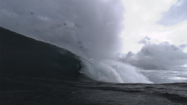 A surfer successfully rides through a wave tube. Available in HD.