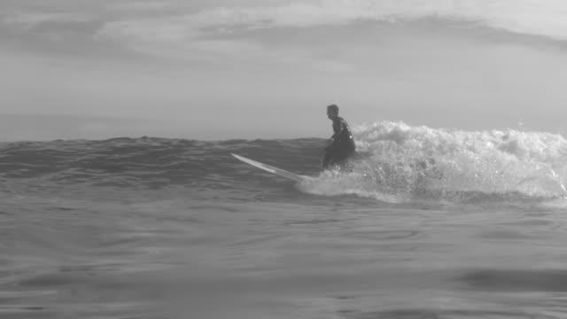 vídeos de stock, filmes e b-roll de a surfer surfing waves on his classic longboard surfboard. - slow motion - diving suit