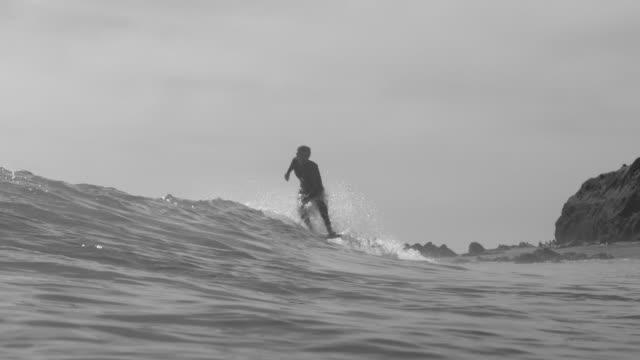 vídeos y material grabado en eventos de stock de a surfer surfing waves on his classic longboard surfboard. - slow motion - surf en longobard
