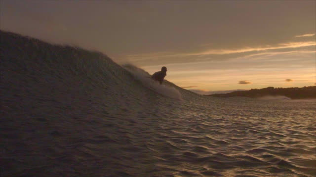 a surfer surfing waves on his surfboard at sunset. - slow motion - skill stock videos & royalty-free footage