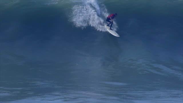vídeos de stock, filmes e b-roll de a surfer surfing waves on his surfboard. - slow motion - diving suit