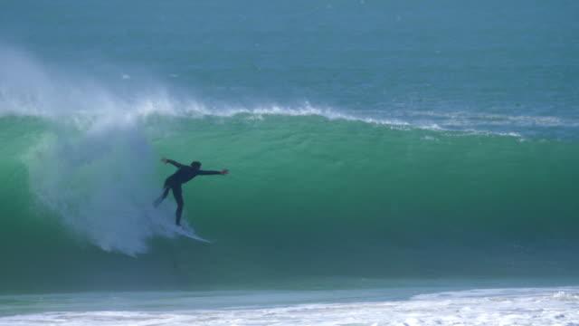 vídeos de stock, filmes e b-roll de a surfer surfing waves on his surfboard. - diving suit