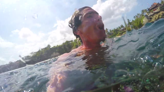 A surfer swimmer taking a selfie in waves and the surf. - Slow Motion