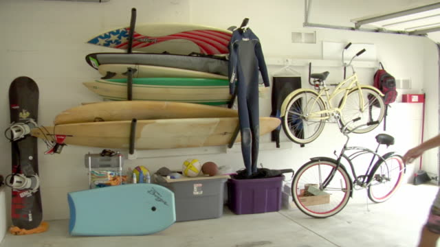 vídeos y material grabado en eventos de stock de ws surfer taking red surf board out if case in garage / manhattan beach, california, usa - red artículos deportivos