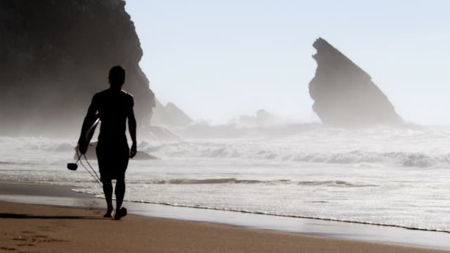 stockvideo's en b-roll-footage met surfer walking at the beach - surfen
